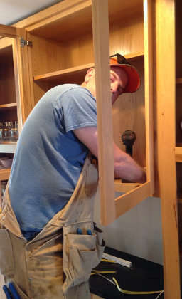 The electrician working on the under-cabinet lighting
