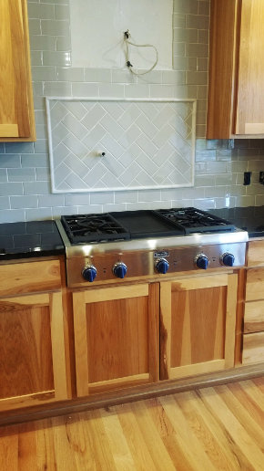 Stove top backsplash, with grout, blue knobs